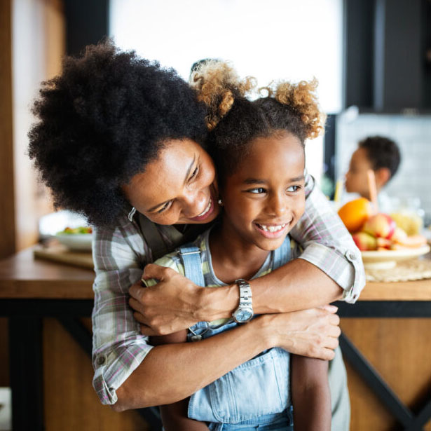 Mother and Daughter hugging in kitchen, with son sitting behind kitchen island